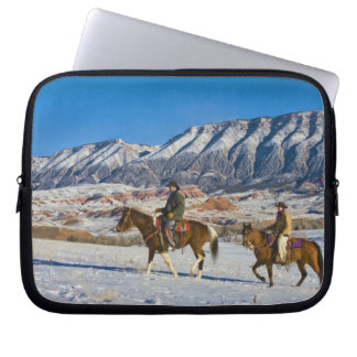 Cowboy and Cowgirl riding Horse through the Snow Laptop Sleeve