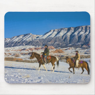 Cowboy and Cowgirl riding Horse through the Snow Mouse Pad
