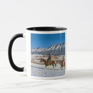 Cowboy and Cowgirl riding Horse through the Snow Mug