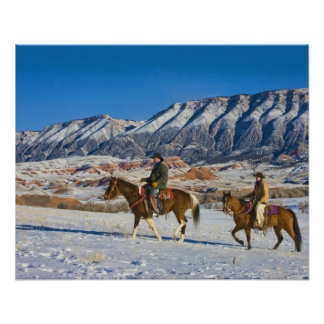 Cowboy and Cowgirl riding Horse through the Snow Poster
