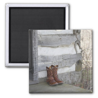Cowboy boots and hat outside of log cabin magnet