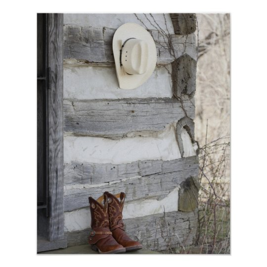 Cowboy boots and hat outside of log cabin