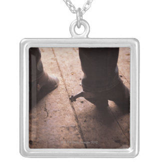 Cowboy boots with spurs on boardwalk at silver plated necklace