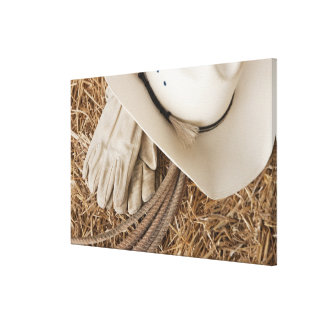 Cowboy hat gloves and rope on haystack canvas print