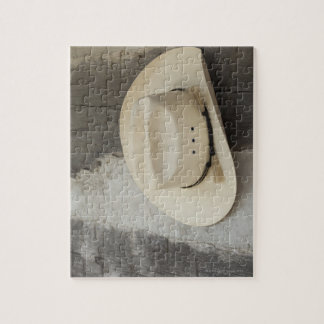 Cowboy hat hanging on wall of log cabin jigsaw puzzle