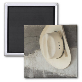 Cowboy hat hanging on wall of log cabin magnet