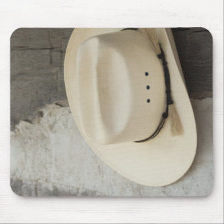 Cowboy hat hanging on wall of log cabin mouse mat