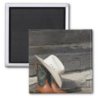 Cowboy hat on cowboy boots outside a log cabin magnet