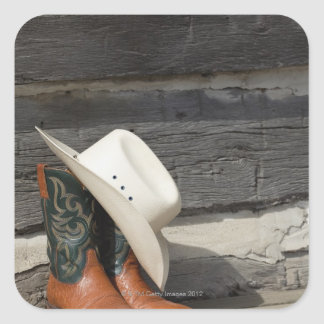 Cowboy hat on cowboy boots outside a log cabin square sticker