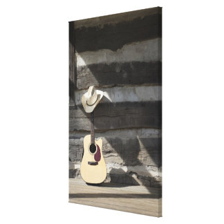 Cowboy hat on guitar leaning on log cabin canvas print