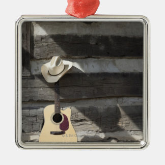 Cowboy hat on guitar leaning on log cabin christmas ornament
