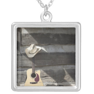Cowboy hat on guitar leaning on log cabin silver plated necklace