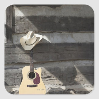 Cowboy hat on guitar leaning on log cabin square sticker