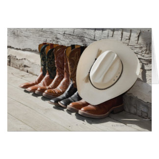 Cowboy hat on row of cowboy boots outside a log card