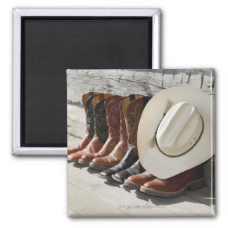 Cowboy hat on row of cowboy boots outside a log magnet