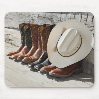 Cowboy hat on row of cowboy boots outside a log mouse pad