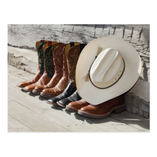 Cowboy hat on row of cowboy boots outside a log postcard