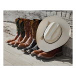 Cowboy hat on row of cowboy boots outside a log poster