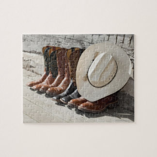 Cowboy hat on row of cowboy boots outside a log puzzles