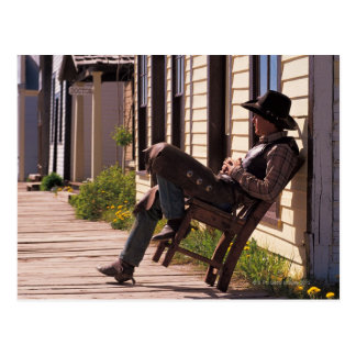 Cowboy in chair on boardwalk in South Park City, Postcard