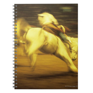 Cowboy riding bucking bronco in rodeo, side view notebook