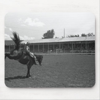 Cowboy riding horse in rodeo, (B&W) Mouse Mat