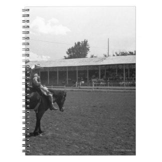 Cowboy riding horse in rodeo, (B&W) Notebook