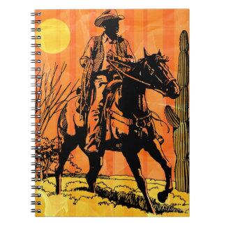 Cowboy riding horseback in desert notebook