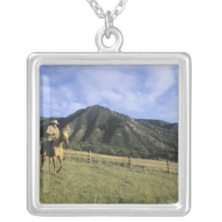 Cowboy riding through field silver plated necklace