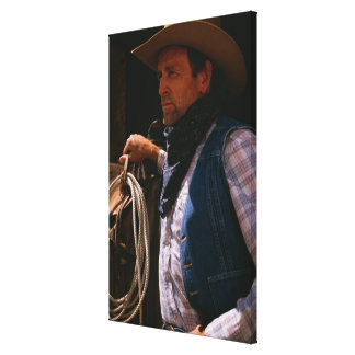 Cowboy standing by saddle with rope canvas print