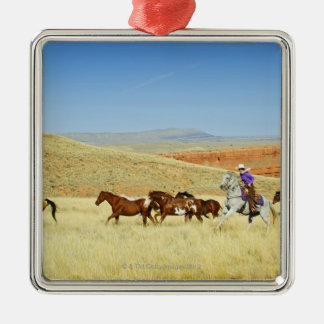 Cowboys herding horses christmas ornament