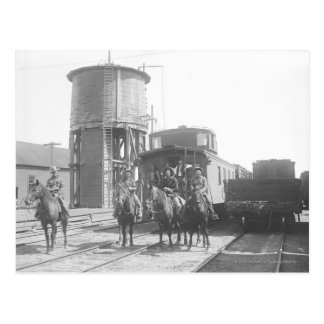Cowboys on horses posing in front of a train postcard