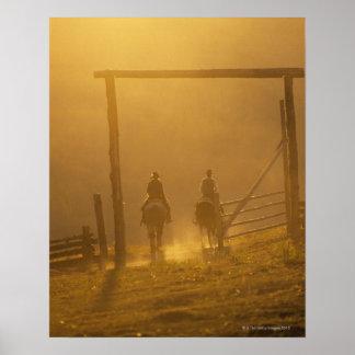 Cowboys riding through gate at dusk print