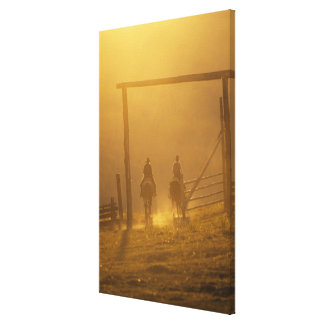 Cowboys riding through gate at dusk stretched canvas prints