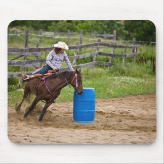 Cowgirl on horseback practicing barrel racing in mouse pad