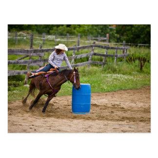 Cowgirl on horseback practicing barrel racing in postcard