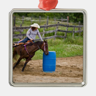 Cowgirl on horseback practicing barrel racing in Silver-Colored square decoration