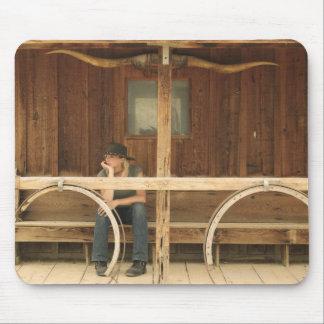 Cowgirl sitting on ranch porch mouse mat