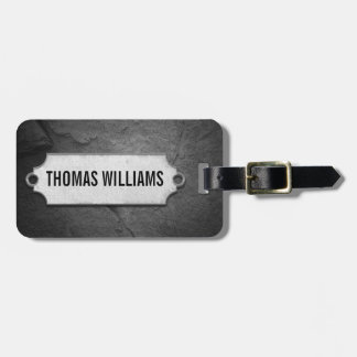 cracked black stone texture with metal tag