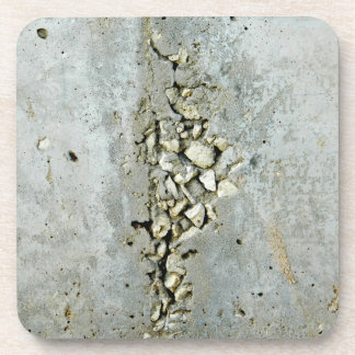 Cracked concrete wall with small stones coaster