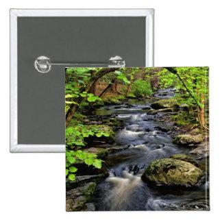 Creek flows through forest 15 cm square badge