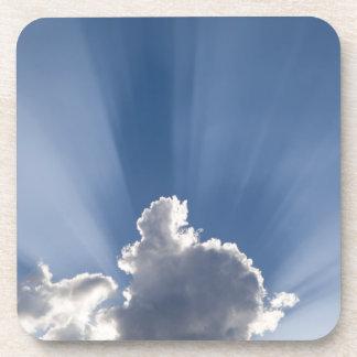 Crepuscular or God's rays streak past cloud. Coaster