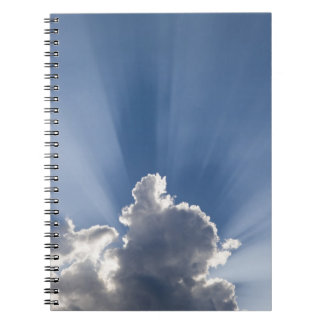 Crepuscular or God's rays streak past cloud. Notebook