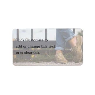 Crossed feet in front of iron fence address label