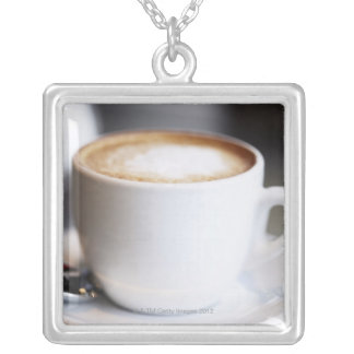 cup of coffee latte on table, close-up silver plated necklace