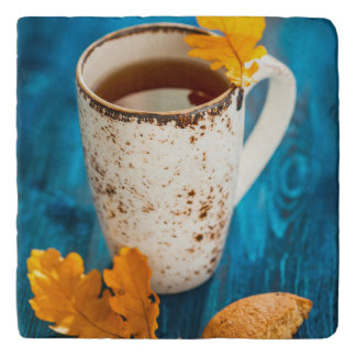 Cup Of Tea And Autumn Leaves On Blue Wooden Trivet
