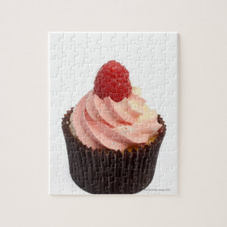 Cupcake topped with raspberry cream and a fresh jigsaw puzzle
