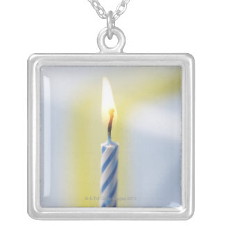 Cupcake with candle, close-up (focus on flame) silver plated necklace