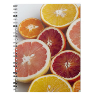 Cut Oranges on table Notebooks