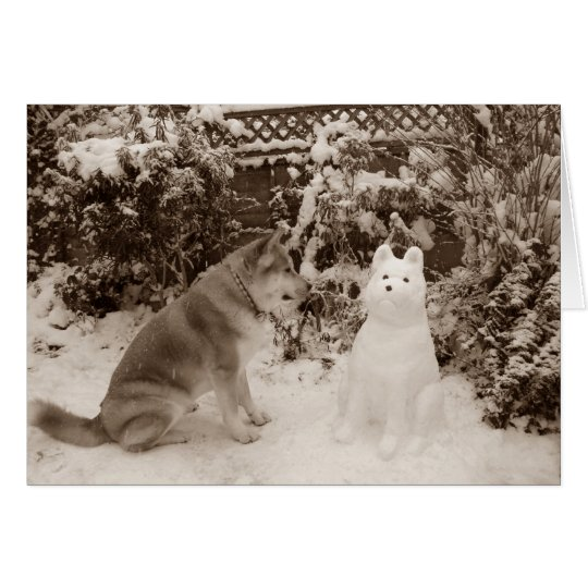 cute akita sitting in snow with snowman dog
